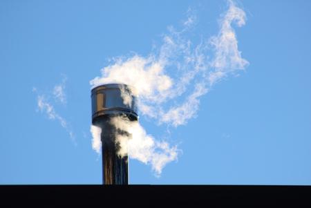 Foto de white smoke comes out of a house chimney, blue sky background and copy space - Imagen libre de derechos