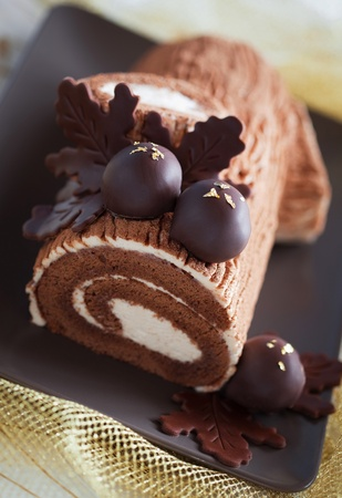 Traditional Christmas Yule Log cake decorated with chocolate chestnuts, selective focus