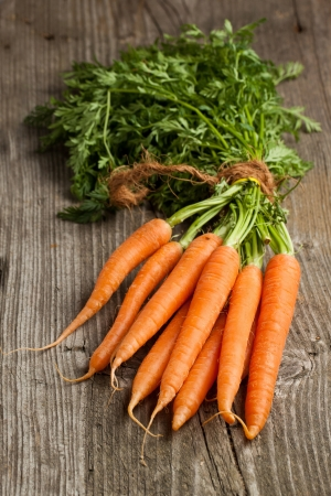 Foto per Freshly washed whole carrots on old wooden table - Immagine Royalty Free