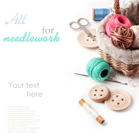 Foto de Basket of threads with wooden buttons and scissors over white with sample text - Imagen libre de derechos