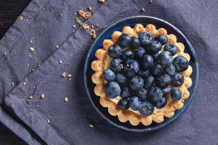 Photo pour Top view on blueberry tart served on blue ceramic plate over textile napkin. - image libre de droit