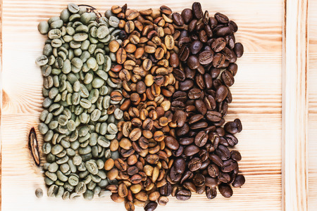 Photo for Green and brown decaf unroasted and black roasted coffee beans over wooden . - Royalty Free Image