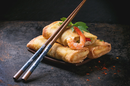 Photo pour Fried spring rolls with vegetables and shrimps, served on squer ceramic plate with chopsticks over black background. - image libre de droit