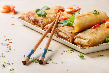Photo pour Fried spring rolls with vegetables and shrimps, served with spicy sauce and chopsticks over white wooden background. - image libre de droit