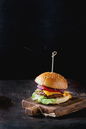 Photo pour Fresh homemade burger on little wooden cutting board over dark background. - image libre de droit