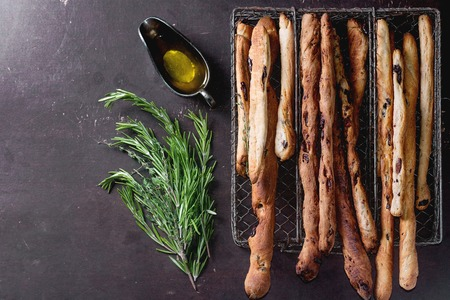 Foto de Fresh baked homemade grissini bread sticks in vintage metal grid box with olive oil and herbs rosemary and thym over dark surface. Top view. - Imagen libre de derechos
