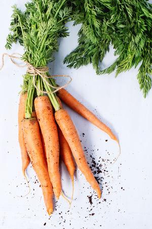 Photo pour Bundle of carrots with soil over light blue wooden background. Top view - image libre de droit