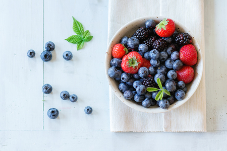 Photo for Spotted ceramic bowl with assortment berries blueberries, strawberries and blackberries at white textile napkin over wooden table. Natural day light. Top view - Royalty Free Image