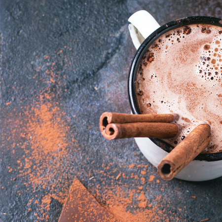 Photo for Vintage mug of hot chocolate with cinnamon sticks over dark background. - Royalty Free Image