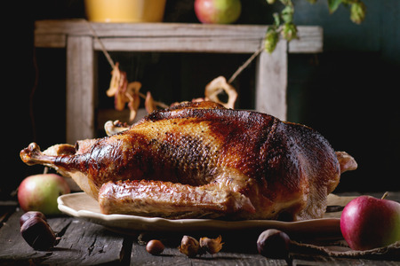 Photo for Roast stuffed goose on ceramic plate with ripe apples over wooden kitchen table. Dark rustic style. - Royalty Free Image