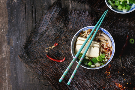 Photo pour Chinese porcelain bowl of asian ramen soup with feta cheese, noodles, spring onion and mushrooms, served with turquoise chopsticks over old wooden table. Dark rustic style. Top view - image libre de droit
