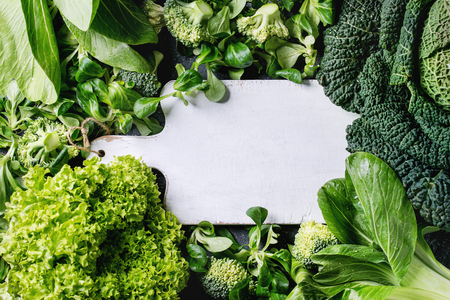 Photo for Variety of raw green vegetables salads, lettuce, bok choy, corn, broccoli, savoy cabbage as frame round empty white chopping board. Food background. Top view, space for text - Royalty Free Image