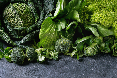 Foto de Variety of raw green vegetables salads, lettuce, bok choy, corn, broccoli, savoy cabbage as frame over black stone texture background. Space for text - Imagen libre de derechos