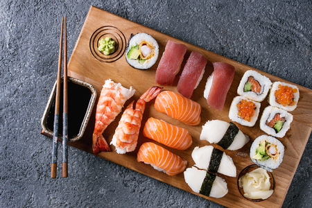 Foto de Sushi Set nigiri and sushi rolls on wooden serving board with soy sauce and chopsticks over black stone texture background. Top view with space. Japan menu - Imagen libre de derechos