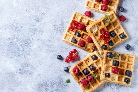 Photo pour Homemade square belgian waffles with fresh ripe berries blueberry, raspberry, red currant over gray texture background. Top view with space - image libre de droit