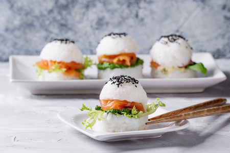 Photo pour Mini rice sushi burgers with smoked salmon, green salad and sauces, black sesame served on white square plate with wooden chopsticks over gray concrete background. Modern healthy food - image libre de droit