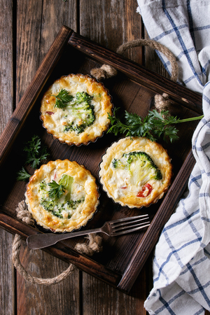 Photo for Baked homemade quiche pie in mini metal forms served with fresh greens, kitchen towel and fork in dark wood tray on old plank wooden background. Flat lay with space - Royalty Free Image