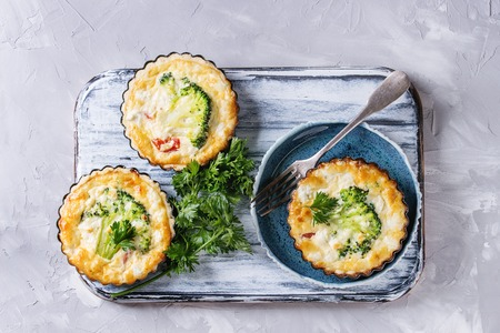 Photo for Baked homemade vegetable broccoli quiche pie in mini metal forms served with fresh greens, plate, fork on white serving board on gray concrete background. Flat lay with copy space. Ready for eat - Royalty Free Image