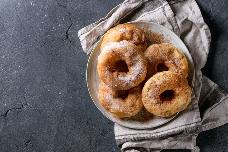 Photo for Plate of homemade donuts with sugar and cinnamon powder on gray textile napkin over dark texture background. Top view with copy space - Royalty Free Image