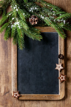 Photo for Vintage empty chalkboard with fir Christmas tree and wood modern decor stars over wooden background. Top view with space for text - Royalty Free Image