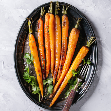 Photo for Roasted young whole carrot with greens and sea salt. Served on vintage metal tray with cutlery over gray concrete texture background. Top view with space. Square image - Royalty Free Image