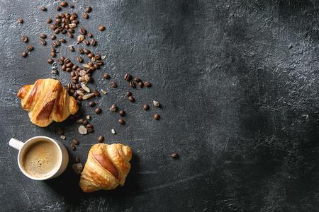 Foto de Fresh baked traditional croissants and mug of espresso coffee, coffee beans, sugar over black texture background. Top view, copy space - Imagen libre de derechos