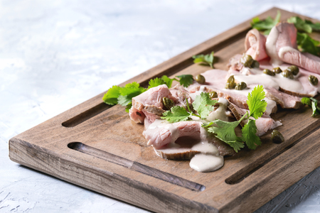 Photo for Vitello tonnato italian dish. Thin sliced veal with tuna sauce, capers and coriander served on wooden serving board over gray texture background. - Royalty Free Image