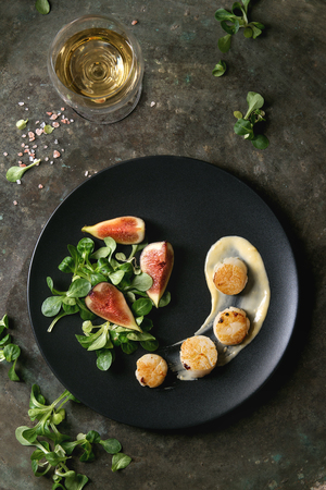 Foto de Fried scallops with lemon, figs, sauce and green salad served on black plate with glass of white wine over old dark metal background. Top view, space. Plating, fine dining - Imagen libre de derechos