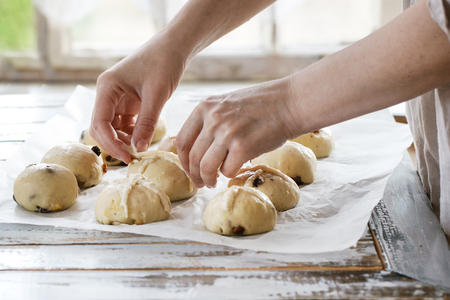 Photo for Raw unbaked buns. Ready to bake homemade Easter traditional hot cross buns on baking paper over white wooden table. Window at background. Female hands make a cross. Natural day light. Rustic style. - Royalty Free Image