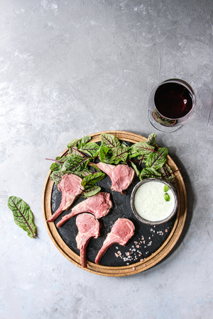 Foto für Grilled sliced rack of lamb with yogurt mint sauce served with green salad young beetroot leaves, glass of red wine, pink salt on round wooden slate board over grey texture background. Top view, space - Lizenzfreies Bild
