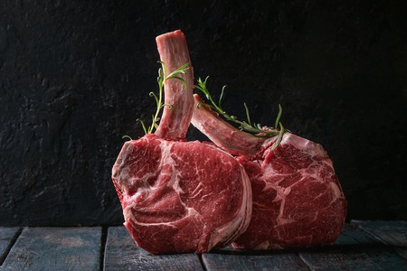Photo pour Raw uncooked black angus beef tomahawk steaks on bones served with rosemary over dark wooden plank table. Rustic style. Close up - image libre de droit