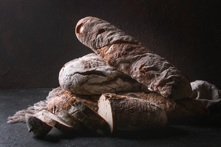 Photo pour Variety of loafs fresh baked artisan rye and whole grain bread on linen cloth over dark brown texture background. Copy space. - image libre de droit