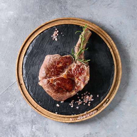 Photo pour Grilled black angus beef tomahawk steak on bone served with salt, pepper and rosemary on round wooden slate cutting board over grey texture background. Top view, copy space. - image libre de droit