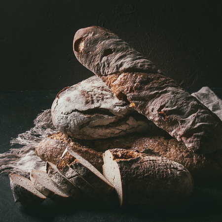 Photo pour Variety of loafs fresh baked artisan rye and whole grain bread on linen cloth over dark brown texture background. Copy space. Square image - image libre de droit