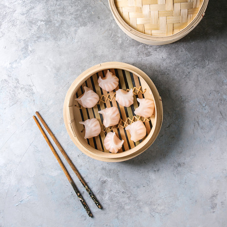 Photo pour Asian steam potstickers dumplings stuffed by shrimps in opened bamboo steamer with chopsticks over grey texture background. Top view, space. Square image - image libre de droit