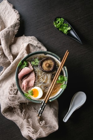Photo for Traditional Japanese Noodle Soup with shiitake mushroom, egg, sliced beef and greens served in ceramic bowl with wooden chopsticks and white spoon on cloth over dark background. Flat lay, space. - Royalty Free Image