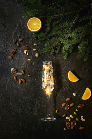 Photo for Christmas lights garland in champagne glass with nuts, orange, fir tree branches over dark texture background. Christmas holiday mood card. Top view with space - Royalty Free Image