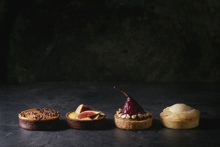 Foto de Variety of sweet tartlets with chocolate, caramel, pears, figs in row on black texture table. - Imagen libre de derechos
