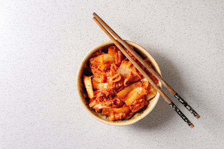 Photo pour Korean traditional fermented appetizer kimchi cabbage salad in ceramic bowl with shopsticks over grey spotted background. Flat lay, space. - image libre de droit