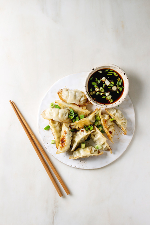 Photo pour Fried asian dumplings Gyozas potstickers in white ceramic plate served with chopsticks and bowl of soy onion sauce over white marble background. Flat lay, space. Asian dinner - image libre de droit