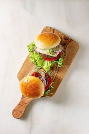 Photo for Two homemade fast food burgers classic hamburger or cheeseburger with beef, salad, cheese and tomato served on wooden cutting board on white marble background. Flat lay, space - Royalty Free Image
