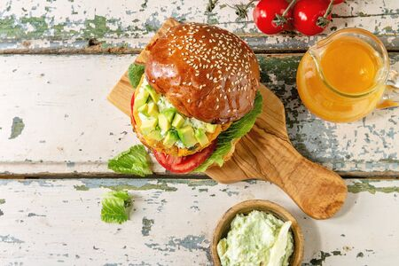 Photo pour Vegan burger with carrot and avocado in classic bun, served on wooden board with avocado sauce and ingredients above on white wood texture background. Flat lay, space. Healthy fast food. - image libre de droit