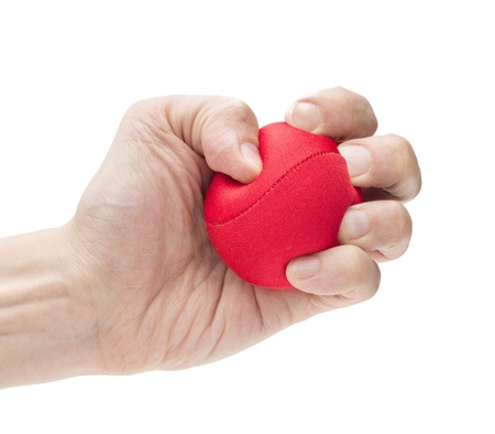Closeup on white background of male hand with tight strong grip applying pressure on red ball