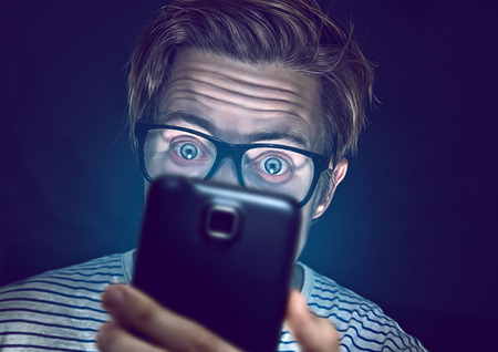 Photo pour   Young man addicted with his smartphone - image libre de droit