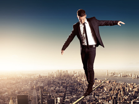 Photo for   Business man walking on high wire in big city  - Royalty Free Image