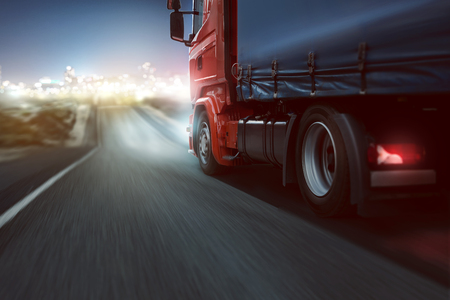 Photo for Truck drives on a country road with bokeh lights in the distance - Royalty Free Image