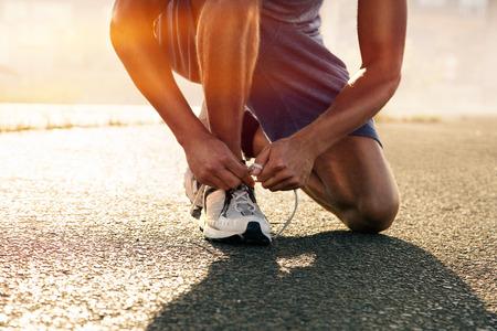 Photo pour Runner ties his shoes - image libre de droit
