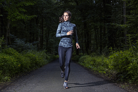 Photo for Runner woman in a dark forest - Royalty Free Image