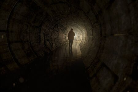 Foto de Man with a torch walks through a tunnel - Imagen libre de derechos