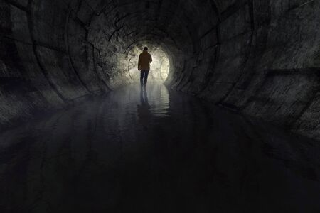 Foto de Man with a torch in a sewer - Imagen libre de derechos